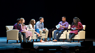 A group of students discusses on stage