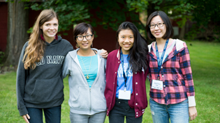 Four female international students posing for a photo outdoors
