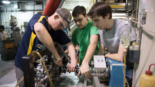 Three males work on engine