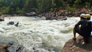 Students sit on rocks and watch white water rafting