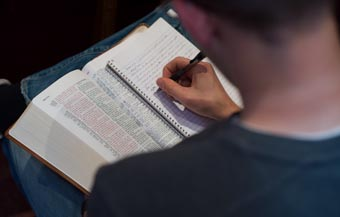 A student studying the Bible and writing notes in a notebook.
