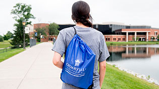 Prospective girl wearing a blue Cedarville drawstring bag on her back walking around the lake.