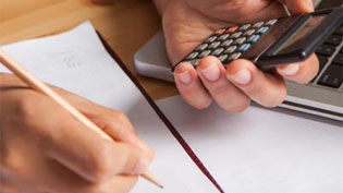 White hands holding a pencil and a calculator over paper on a desk