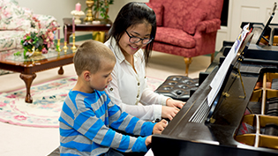 Female student plays piano with child