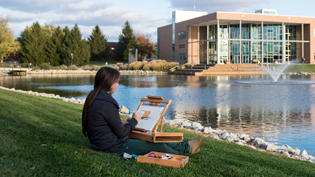 A female student paints by the lake