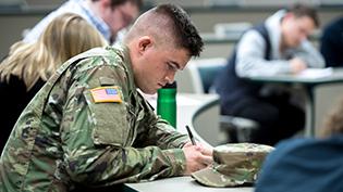 Man in army uniform taking notes in class.