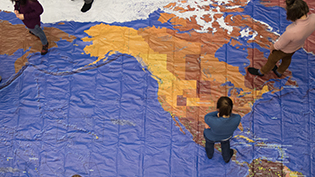 Cedarville students stand on a map of the United States