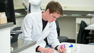 Male pharmacy student reads a label on a bottle