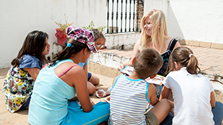 Female student talking with Spanish speaking children