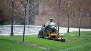 A student worker mowing the grass on campus