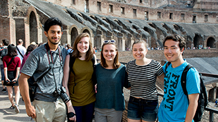 Students stand in front of colosseum