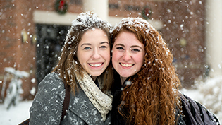 Two female students smile in the snow