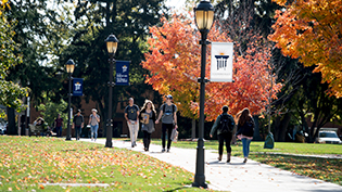 Students walk through Cedarville's scenic campus during the fall