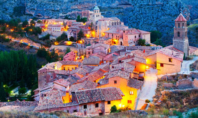 Photograph looking down upon the glowing golden-yellow lit town of Albarracín, Spain as seen from the surrounding hillside.