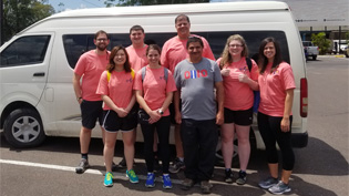A group pf faculty and students in front of a van wearing  matching shirts