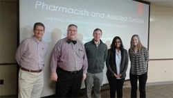 "Five people posing in front of a powerpoint with a slide that says, ""Pharmacists and assisted suicide"""