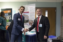 Two men handshake in front of information tables at a career fair