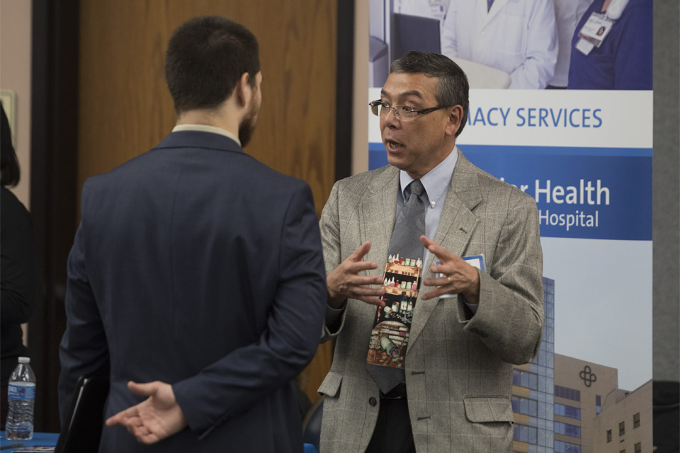 Richard talking to a man in a suit at an academic fair