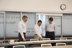 3 professors look at unrolled scroll on table
