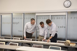 3 professors look at Torah scroll unrolled on table