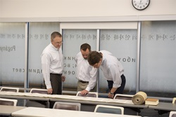 3 professors looking at the Torah Scroll on a table
