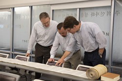 3 professors point and discuss torah scroll