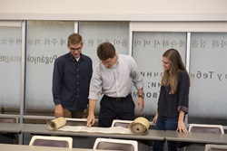 Dr. Shepherd and students look at partially opened Torah scroll
