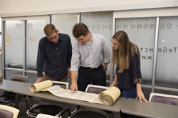 2 students with Dr. Shepherd look at partially open Torah scroll