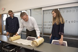 Dr. McKinion and 2 students start to unravel Torah Scroll