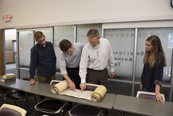 2 students with Dr. Shepherd and Dr. McKinion look at partially open Torah scroll