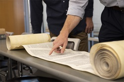 Torah Scroll rolled out on table with people pointing and analyzing it