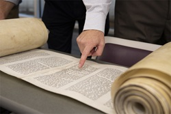 Torah Scroll partially rolled out on table with people pointing and analyzing it