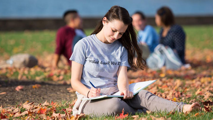 female student sitting in grass in the fall writing in a notebook