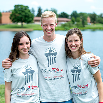 Three college now students stand by lake