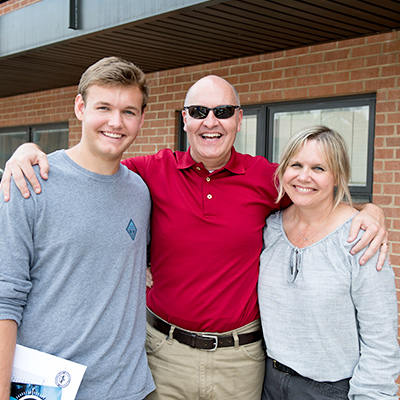 Parents pose for a picture with their college now student