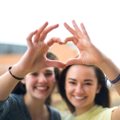 Two female students make a heart with their hands