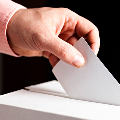 Peron places a slip of paper in a voting box