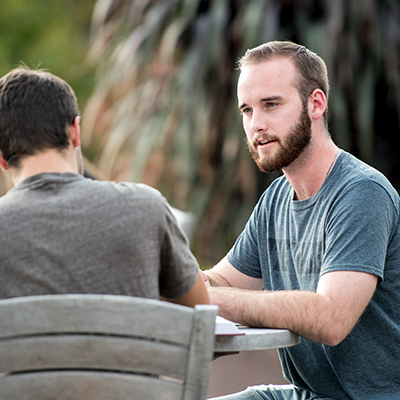 Two male students having a discussion outside the Center for Biblical and Theological Studies