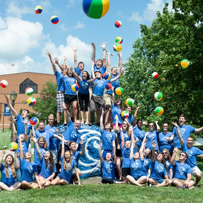 picture of students celebrating on the Cedarville rock while wearing cove shirts and tossing beach balls in the air