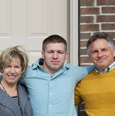 Two parents with college son in the middle standing outside the door, smiling