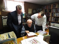 Drs. Warren Wiersbe, Thomas White and Jason Lee looking at an open book in the Wiersbe basement library.