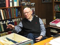 Dr. Warren Wiersbe gesturing with his hand while sitting in his basement library.