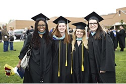Four students in cap and gown at commencement
