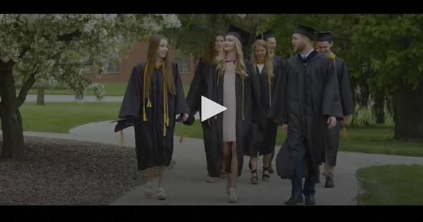 Video screenshot of graduates walking on sidewalk