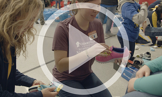 Video screen shot of nursing students helping children try on shoes