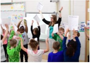 education major in classroom with young students with hands raised and papers in hand