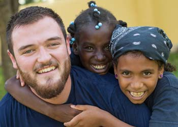 A man works with 2 children on a missions trip.