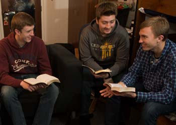 Three male students gather in a softly lit dorm room to study the Bible