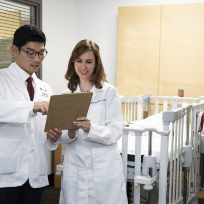 Physicians in white lab coats reviewing records on a clipboard.