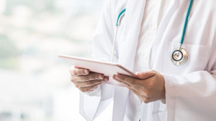 Doctor in a white coat holding a tablet.